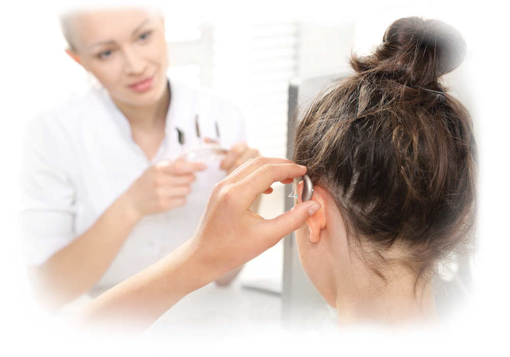 A younger woman gets fitted for hearing aids by her female audiologist